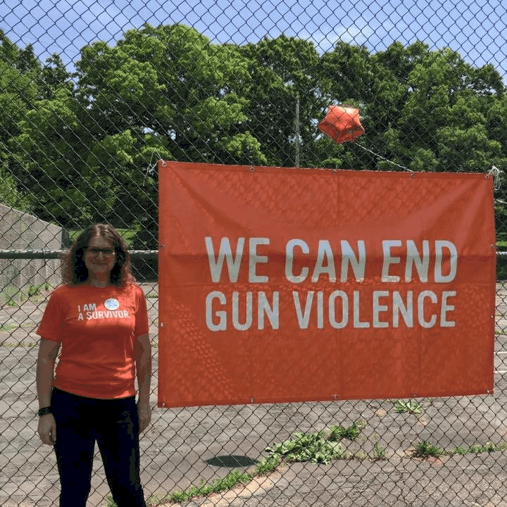"Jarren Peterson in front of a sign that says ""We can end gun violence"""